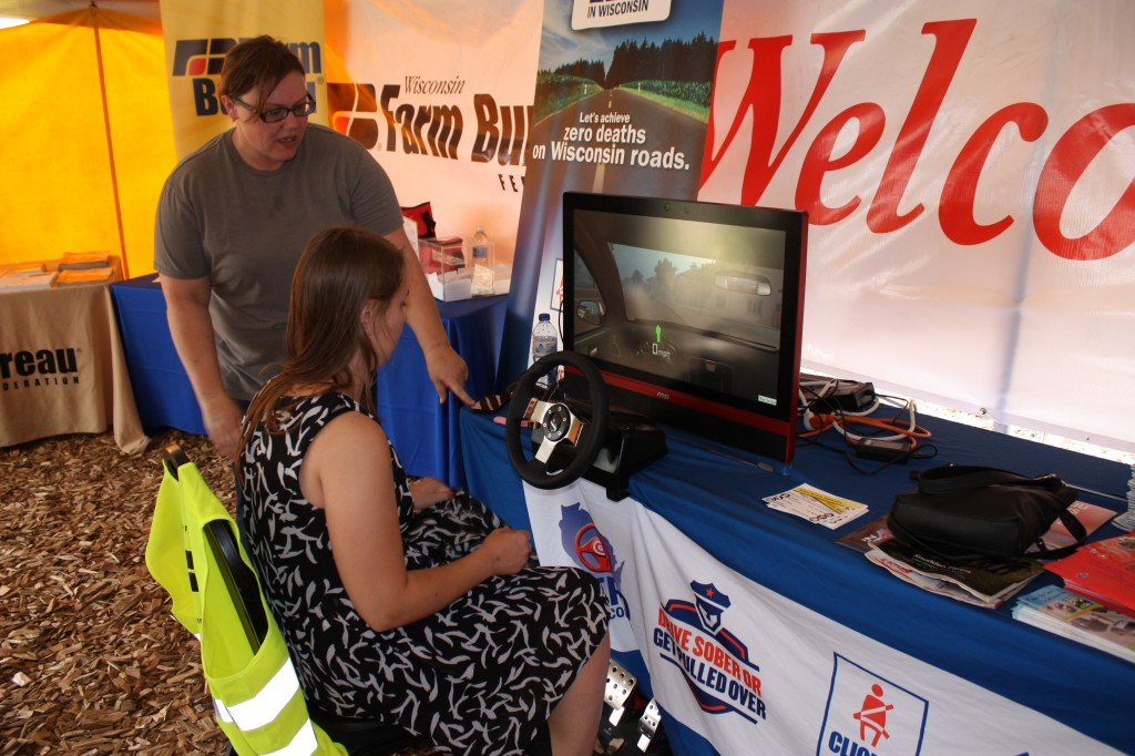 Theresa Nelson guides an operator through the simulator at Farm Tech Days 2016.