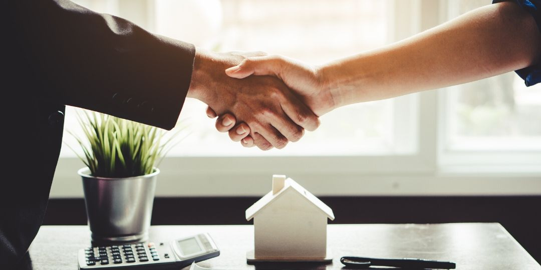 Landlord and tenant shaking hands after agreeing on renters insurance